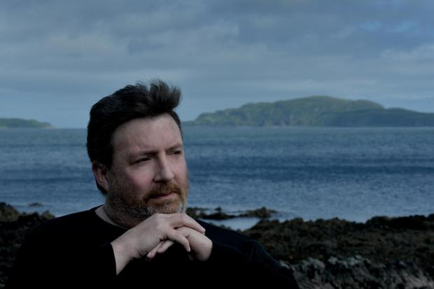 HeraldScotland: Author Denzil Meyrick in Campbeltown with Southend on the Kintyre peninsula in the background. Picture: Kirsty Anderson