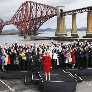 HeraldScotland: Scotland's First Minister Nicola Sturgeon poses with newly-elected SNP MPs in front of the Forth Bridge in Queensferry