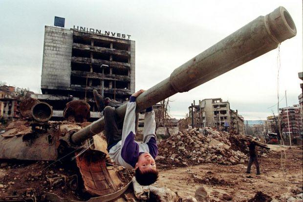 Above, in 1996, children played among the debris of war in siege-hit Sarajevo. Right, a boy holds the remains of a mortar picked up in Homs last week Main photograph:  Odd Andersen/AFP/ Getty Images Free Syrian Army fighters have captured arms, including