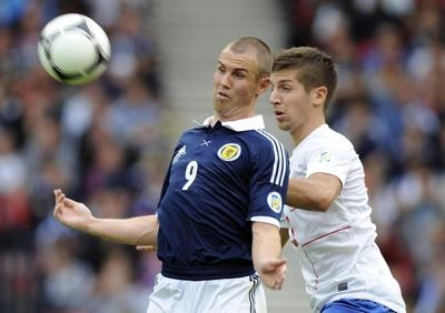 Kenny Miller struggles to win a header against Serbia