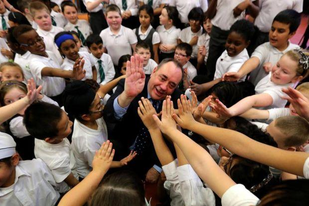 HIGH-FIVES: Alex Salmond helps pupils celebrate the 50th birthday of St Patrick's Primary School in Glasgow yesterday. Picture: PA
