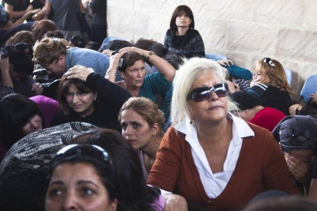 SHELTER: Mourners take cover as air raid sirens warn of incoming Hamas rockets during a funeral in the Israeli town of Kiryat Malachi. Picture: Reuters