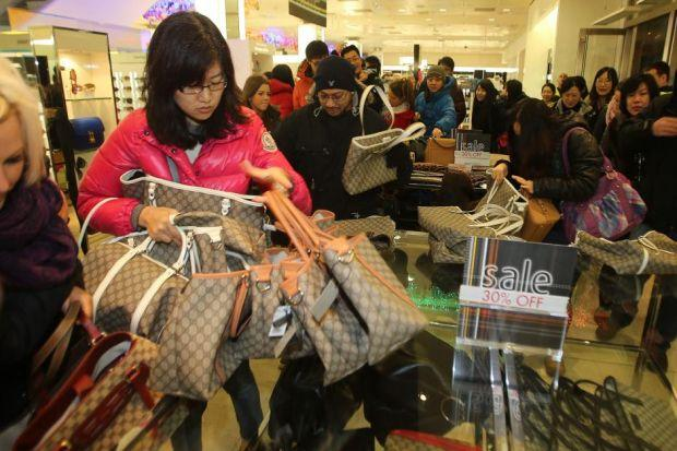 BUYING FRENZY: A young woman snaps up a selection of cut-price handbags at the Harvey Nichols sale in Edinburgh. Picture: Gordon Terris