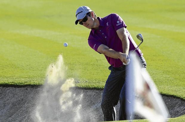 Joint leader Justin Rose splashes out of a bunker during yesterday's first round. Picture: EPA
