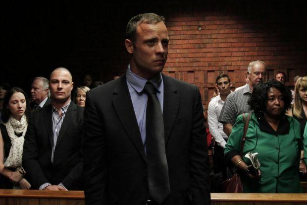 accused: Oscar Pistorius awaits the start of court proceedings in Pretoria while his brother Carl, left, looks on. Picture: Reuters