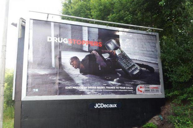 UNDER FIRE: The controversial poster which shows a black drug dealer pinned to the ground by a telephone has been put on display at various different sites across Scotland's biggest city.