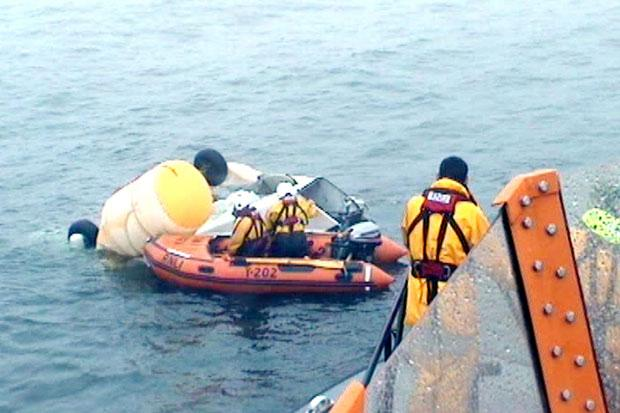 RNLI volunteers and Coastguard inspecting the wreckage of the Super Puma L2 helicopter