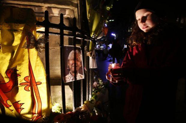 LIGHT IN THE DARK: The Mandela memorial at Nelson Mandela Place in Glasgow. Erin Stewart, nine, from Newlands, with a candle beside the flowers and tributes as the city reveres a man of legend. Picture Martin Shields