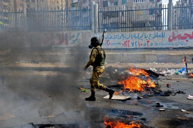 An Egyptian soldier walks through a burning street in Alexandria after clashes with supporters of ousted President Mohammed Mursi, right