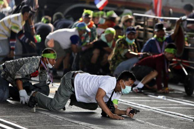 Masked anti-government protesters crouch during a gunfight in Bangkok	Photograph: Nir Elias/Reuters