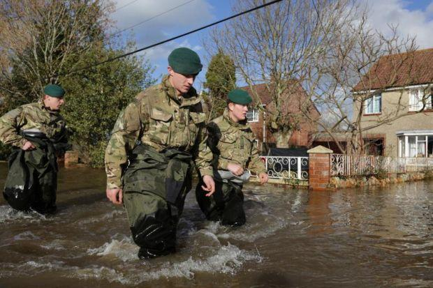 WADING IN: Royal Marines helped evacuate families from flooded homes in the Somerset village of Moorland. Picture: Matt Cardy/Getty Images