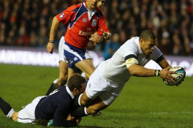 Luther Burrell dives over for the first of England's tries, despite the desperate efforts of Greig Laidlaw Photograph: Stewart Attwood
