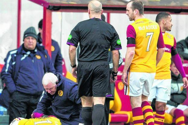 Motherwell's Keith Lasley receives treatment for an injured knee with 10 minutes played. Picture: SNS