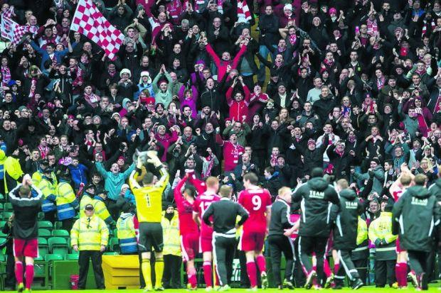 The Aberdeen players celebrate in front of their fans  at Parkhead. Picture: SNS
