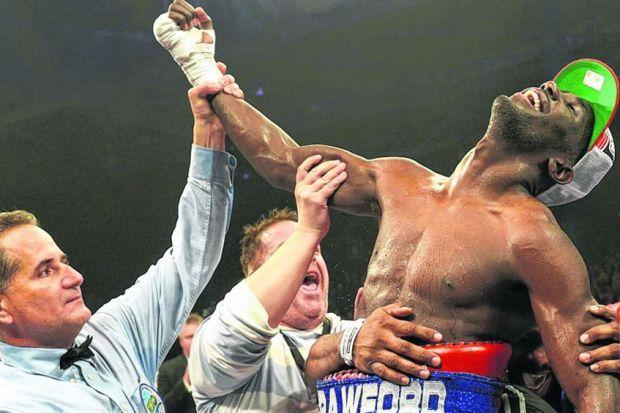 Terence Crawford is held aloft after defeating Ricky Burns by unanimous points decision on Saturday. Picture: SNS