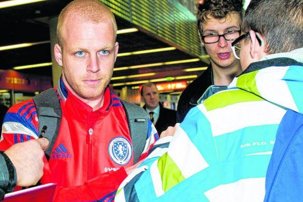 Steven Naismith's autograph is in demand as he arrives at Warsaw Chopin Airport with the Scotland squad yesterday. Picture: Craig Williamson/SNS