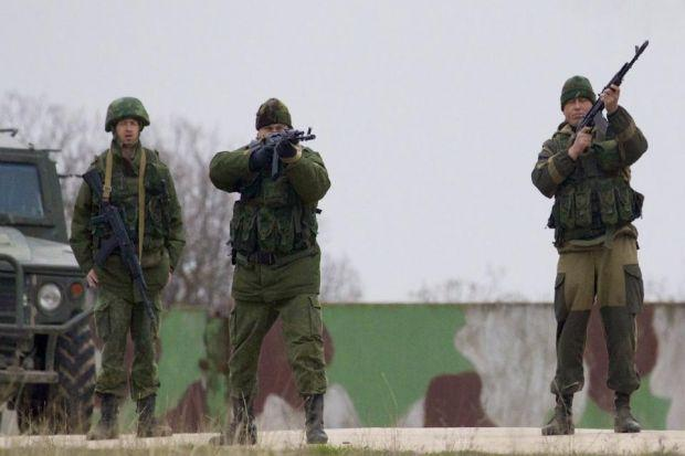 ARMED: Russian soldiers fire warning shots at an air base in Ukraine.