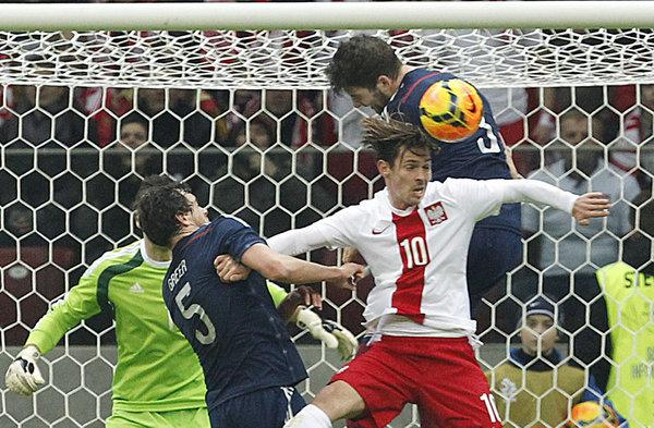 Poland's Ludovic Obraniak, front, and Scotland's Gordon Greer, left, and Charlie Mulgrew, top, challenge for the ball