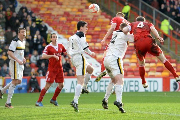 Adam Rooney leaps highest to head Aberdeen in front at Pittodrie. Picture: SNS