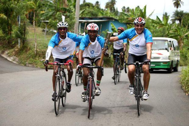 RELAY CONTINUES: Shimano Bailey, centre, from the St Vincent and the Grenadines Cycling Union, rides with the Queen's Baton in Kingstown.