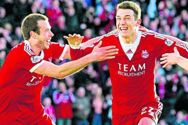 Ryan Jack, centre, celebrates with Andrew Considine after hitting the winner for Aberdeen Photograph: SNS