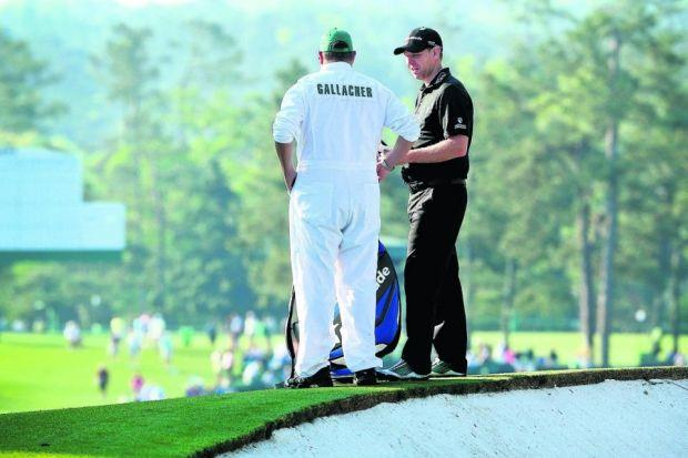 Stephen Gallacher discusses his next shot with caddie Damian Moore on his way to a making par on the second day at Augusta. Picture: Getty Sport