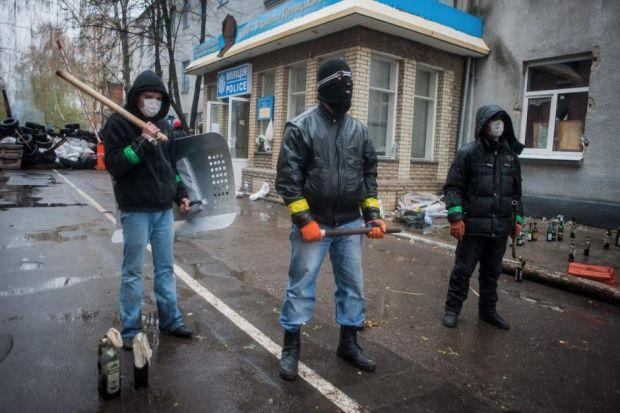 MENACING: Pro-Russian armed protesters stand guard in front of an occupied police station in the Ukrainian city of Slaviansk. Picture: EPA/Roman Pilipey