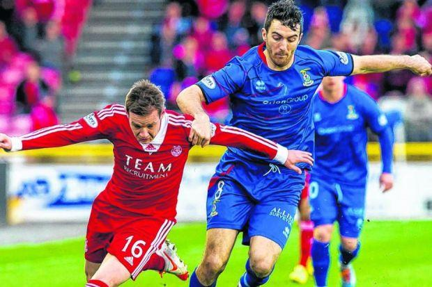 Going nowhere fast: Ross Draper pulls at the arm of Peter Pawlett as the Aberdeen attacker surges forward. Picture: SNS