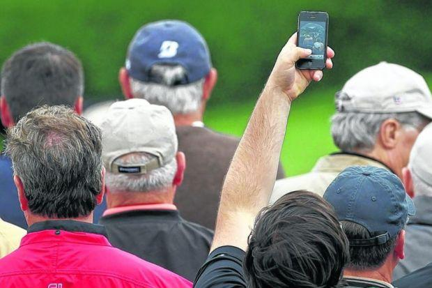 Say cheese: But the ever-present mobile phone means that watching live golf has lost much of its endearing mystery. Picture: Getty Images