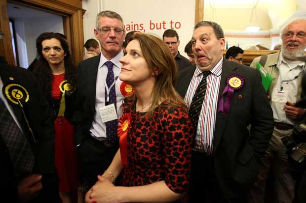 UKIP MEP David Coburn pulls a face behind Labour MEP's Catherine Stihler and David Martin at the City Chambers in Edinburgh