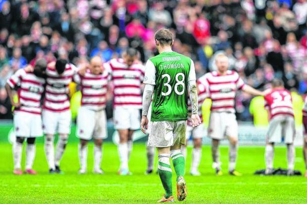 Kevin Thomson makes his way back to the centre circle after missing the first penalty of the shoot-out. Jason Cummings missed another as Hibs dropped out of the top flight. Picture: SNS
