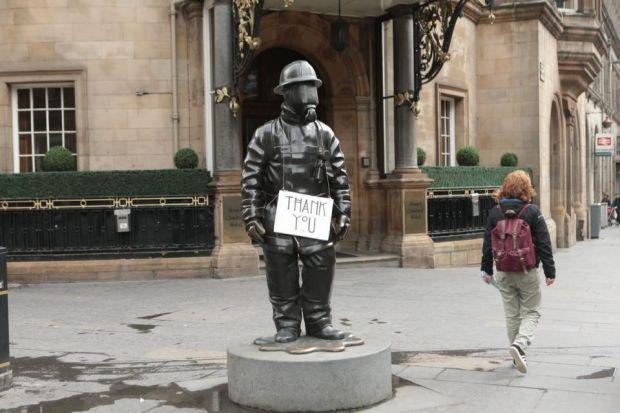 Grateful:  A fireman's statue displays the thanks of a city as a young girl looks on.