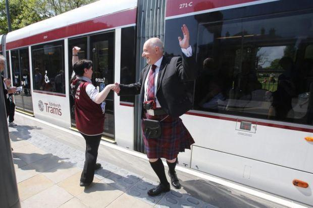 Left, Tram fan Martin Hague from Rotherham with 'clippy' Marj Griffiths celebrate the start of trams in Edinburgh. Above, Alan Taylor and others join the first tramPhotographs: Gordon Terris