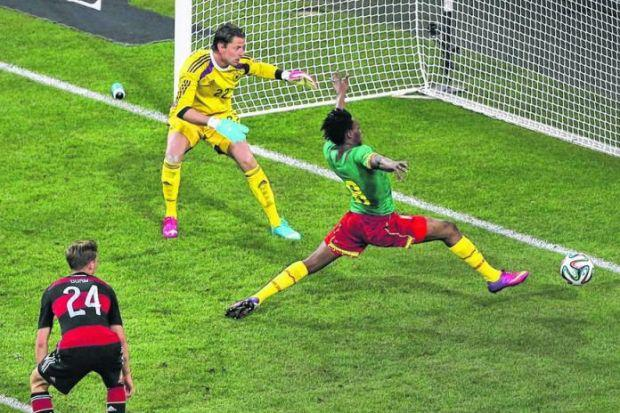 Benjamin Moukandjo stretches out a leg to make sure a shot by Samuel Eto'o (out of picture) beats German goalkeeper Roman Weidenfeller for the opening goal last night. Picture: EPA