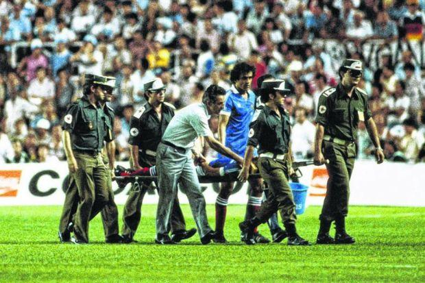 Patrick Battison, flanked by Michel Platini, is carried off in the 1982 semi-final with West Germany. Picture: Getty