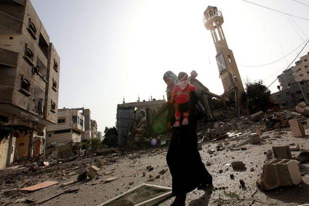 A Palestinian woman carries a child as she makes her way through rubble in front of the destroyed Al-Tawfeeq mosque following an airstrike in Al-Nusairat refugee camp in the central Gaza StripPhotograph: EPA/Mohammed Saber