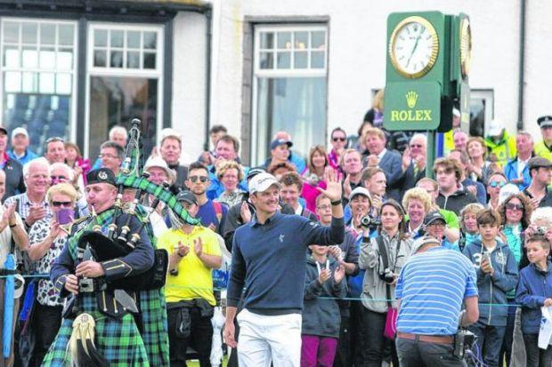 A piper leads the way as Justin Rose walks to the 18th green at Balgownie to collect the trophy. Picture: Colin Mearns