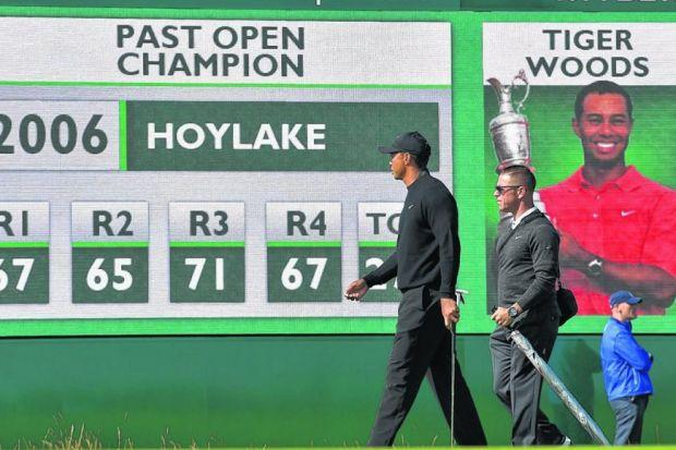 MEMORY LANE: Tiger Woods and his coach Sean Foley walk past a scoreboard which carries his name and status as last Open champion at Hoylake. Picture: Getty Sport
