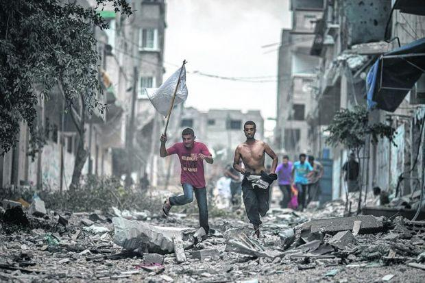 ESCAPE: Two Palestinian men with a white flag flee their Gaza homes in a brief ceasefire requested by rescuers to retrieve bodies. Picture: Oliver Weiken