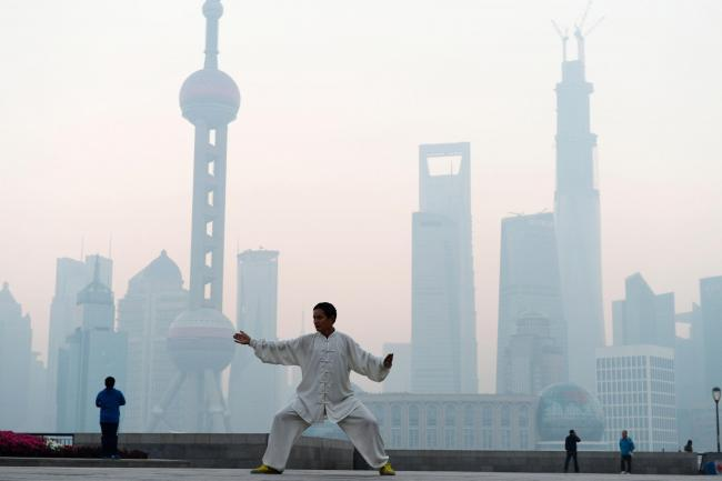 SHANGHAI, CHINA - NOVEMBER 07:  (CHINA OUT) A man practices Tai Chi at the Bund as heavy smog engulfs the city on November 7, 2013 in Shanghai, China. People were advised to stay indoors today as the Shanghai Environment Agency measured air pollution leve