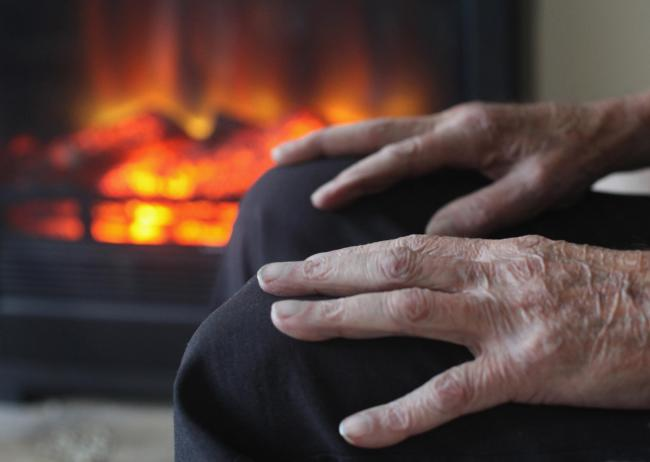 BRISTOL, ENGLAND - OCTOBER 06:  In this photo illustration, an elderly man warms himself in front of a fire on October 6, 2011 in Bristol, England. Energy price rises and an increase in the cost of living has resulted in more people, including the elderly