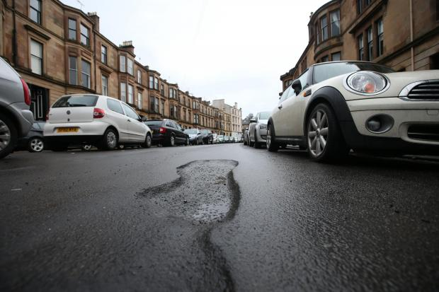 HeraldScotland: Potholes on Dowanhill Street, in Glasgow's west end, photo: Colin Templeton