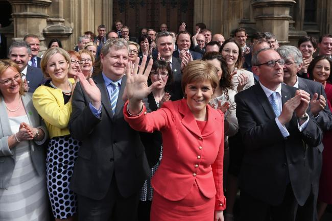 First Minister and leader of the SNP Nicola Sturgeon is joined by the newly elected SNP members of parliament outside the Houses of Parliament on May 11, 2015