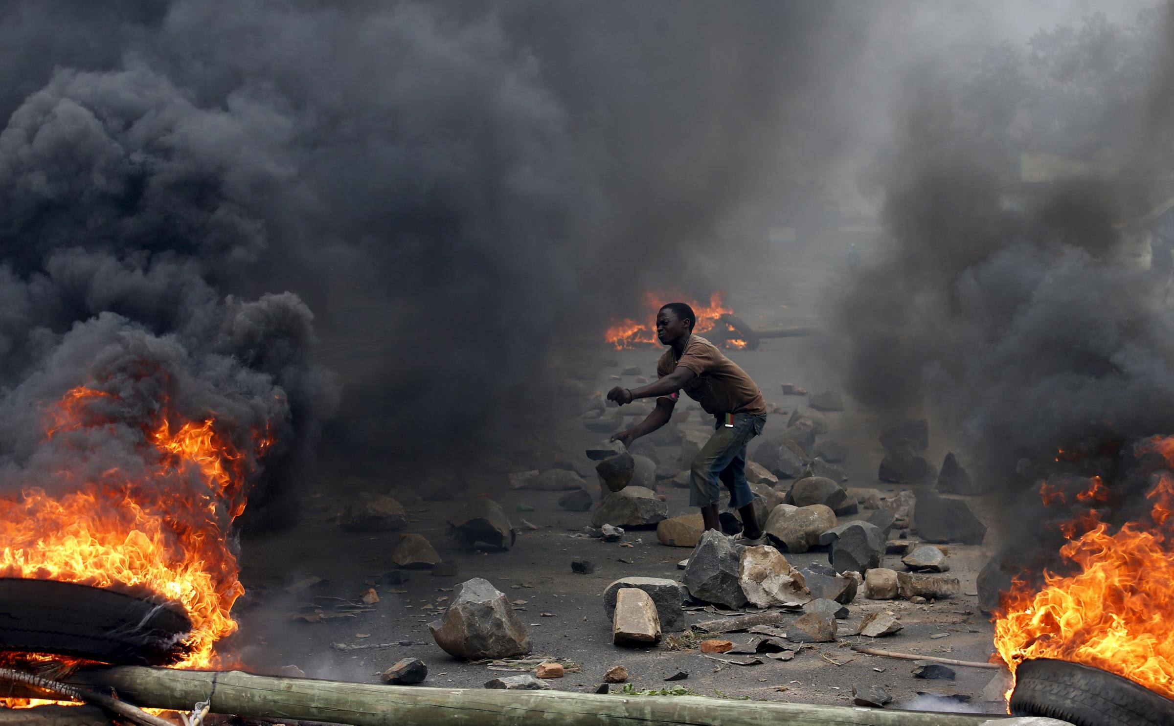 A protester sets up a  barricade during a protest against Burundi President Pierre Nkurunziza and his bid for a third term in Bujumbura, Burundi, in this May 22, 2015 file photo. The European Union mission in Burundi is temporarily making a small reductio