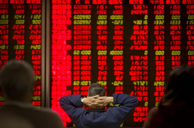 Chinese investors monitor stock prices in a brokerage house in Beijing last week.