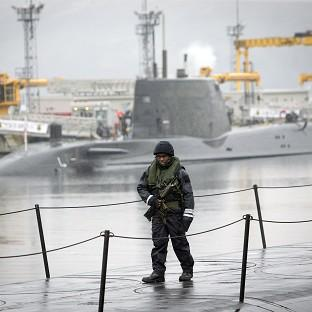 HeraldScotland: A member of the armed services walks on the deck of Vanguard-class submarine HMS Vigilant