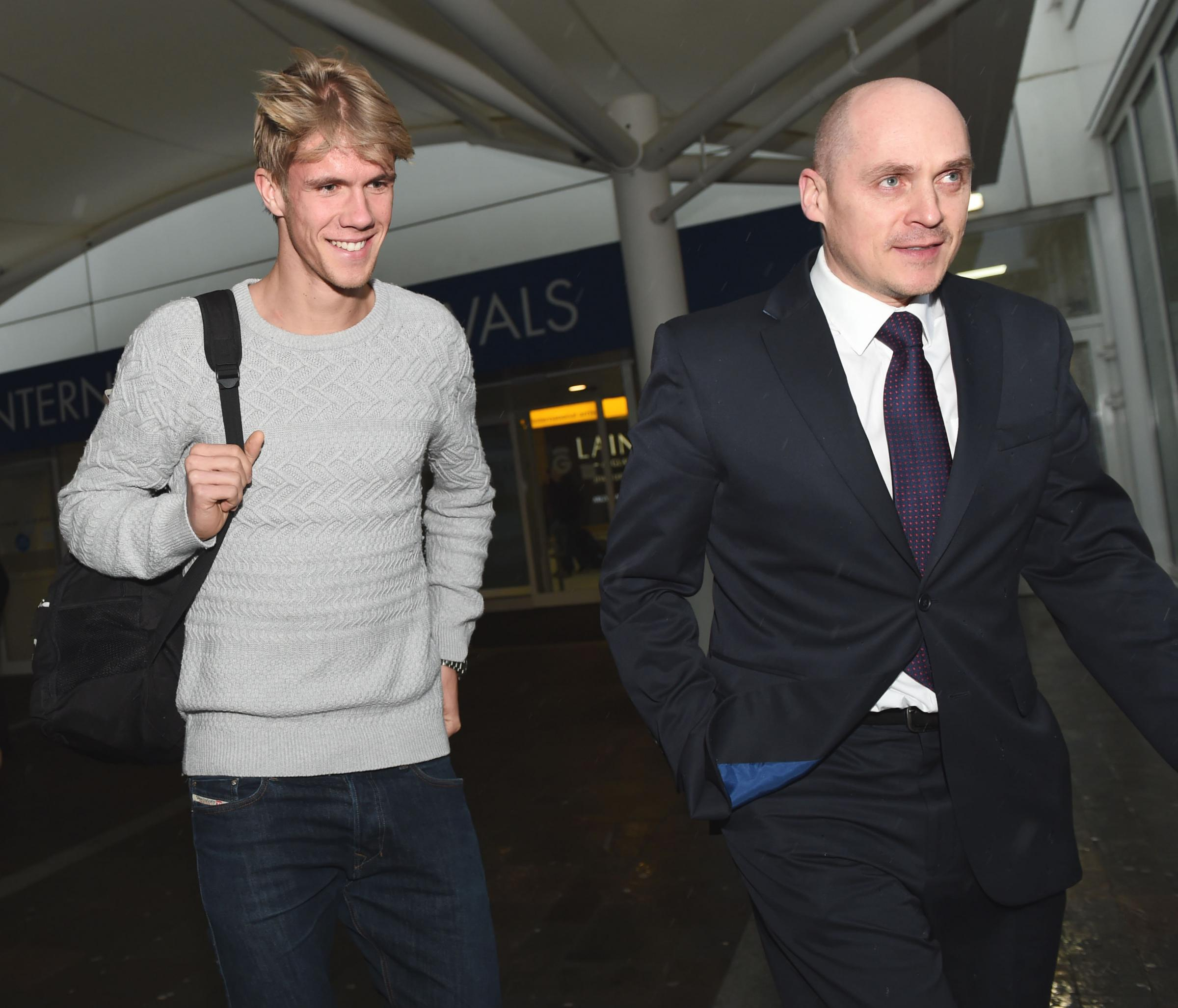 THE BHOY IS BACK IN TOWN: Kristoffer Ajer is escorted out of Glasgow Airport by Celtic physiotherapist Tim Williamson after flying in for talks