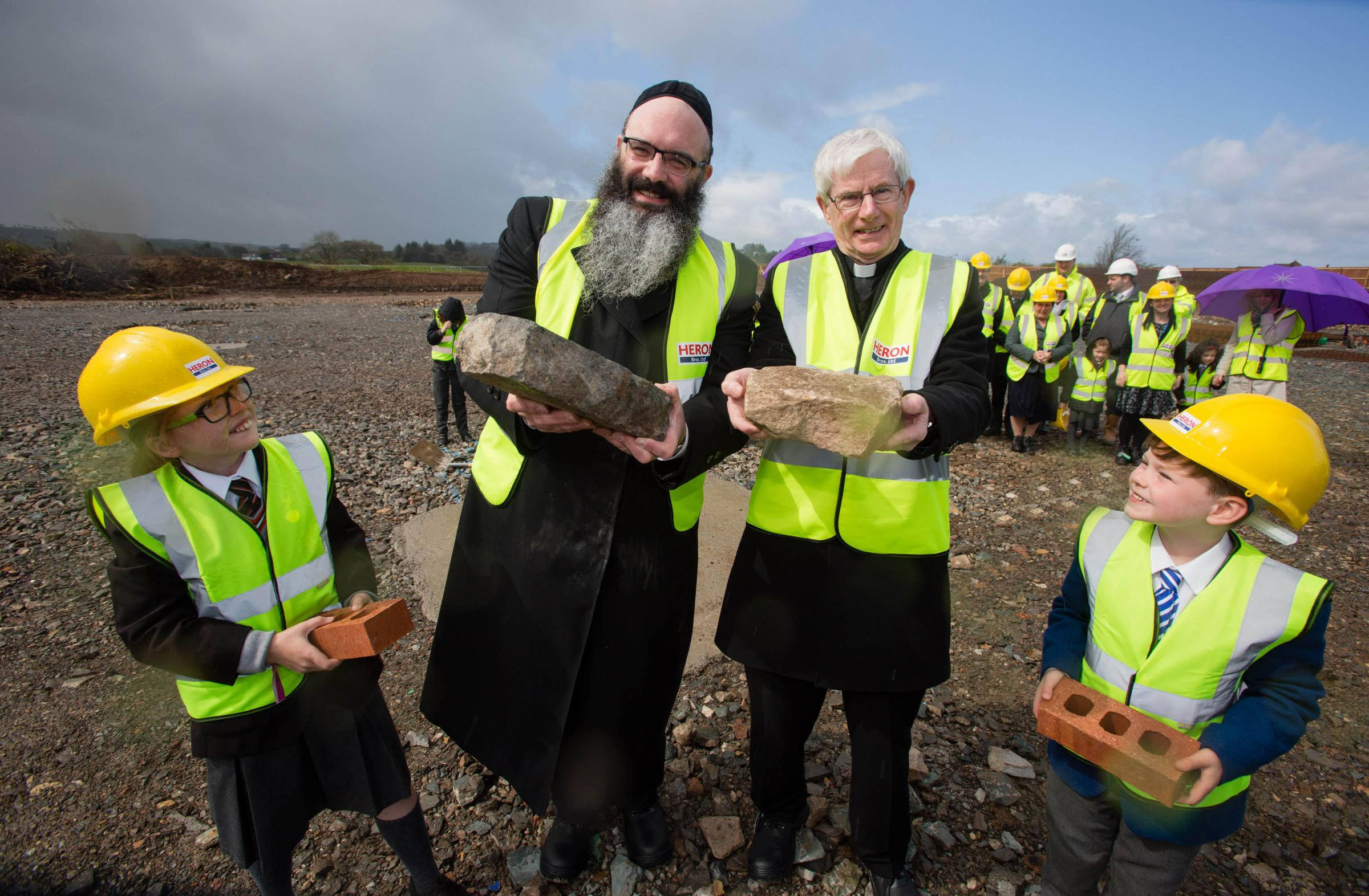 Rabbi Rubin of Giffnock Synagogue and St Cadoc's Parish Priest Monsignor Monaghan holding ceremonial stones laid on the site of a new joint faith schools campus being built in Newton Mearns