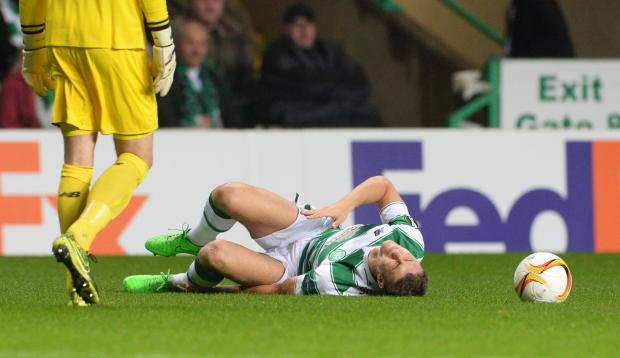 HeraldScotland: Celtic's Jozo Simunovic lies on the ground after picking up an injury.