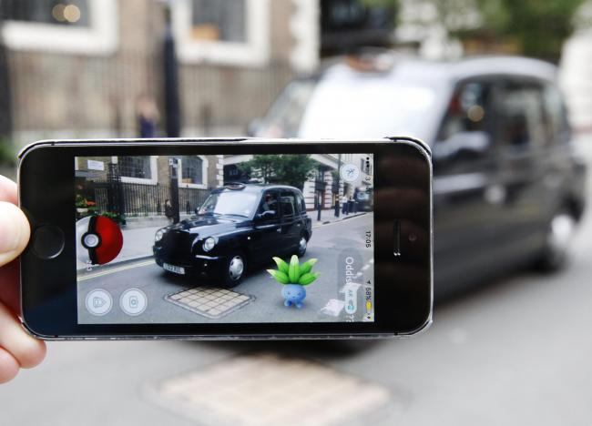 An Oddish Pokemon character appears in front of a London taxi during a game of Pokemon Go. Photo by Olivia Harris/Getty Images